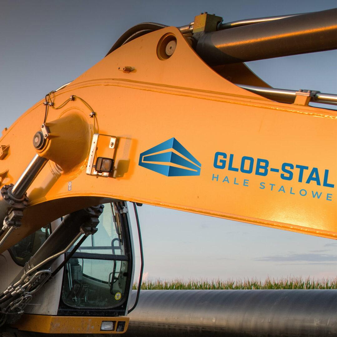 Koparka z projektem graficznym logo firmy produkcyjnej #glob-stal