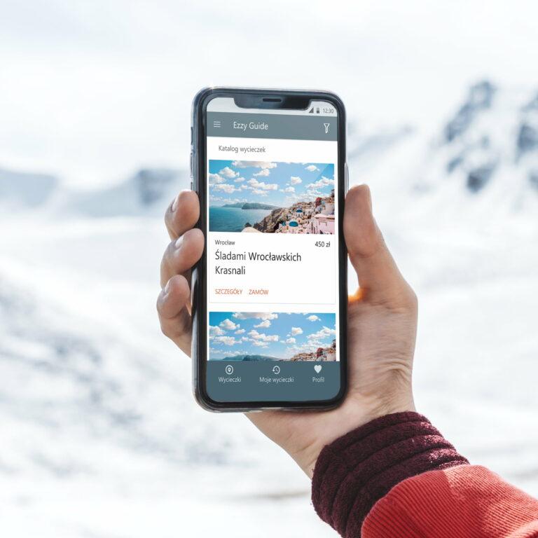 Mężczyzna trzyma w rękach telefon z uruchomioną aplikacją #ezzy-guide