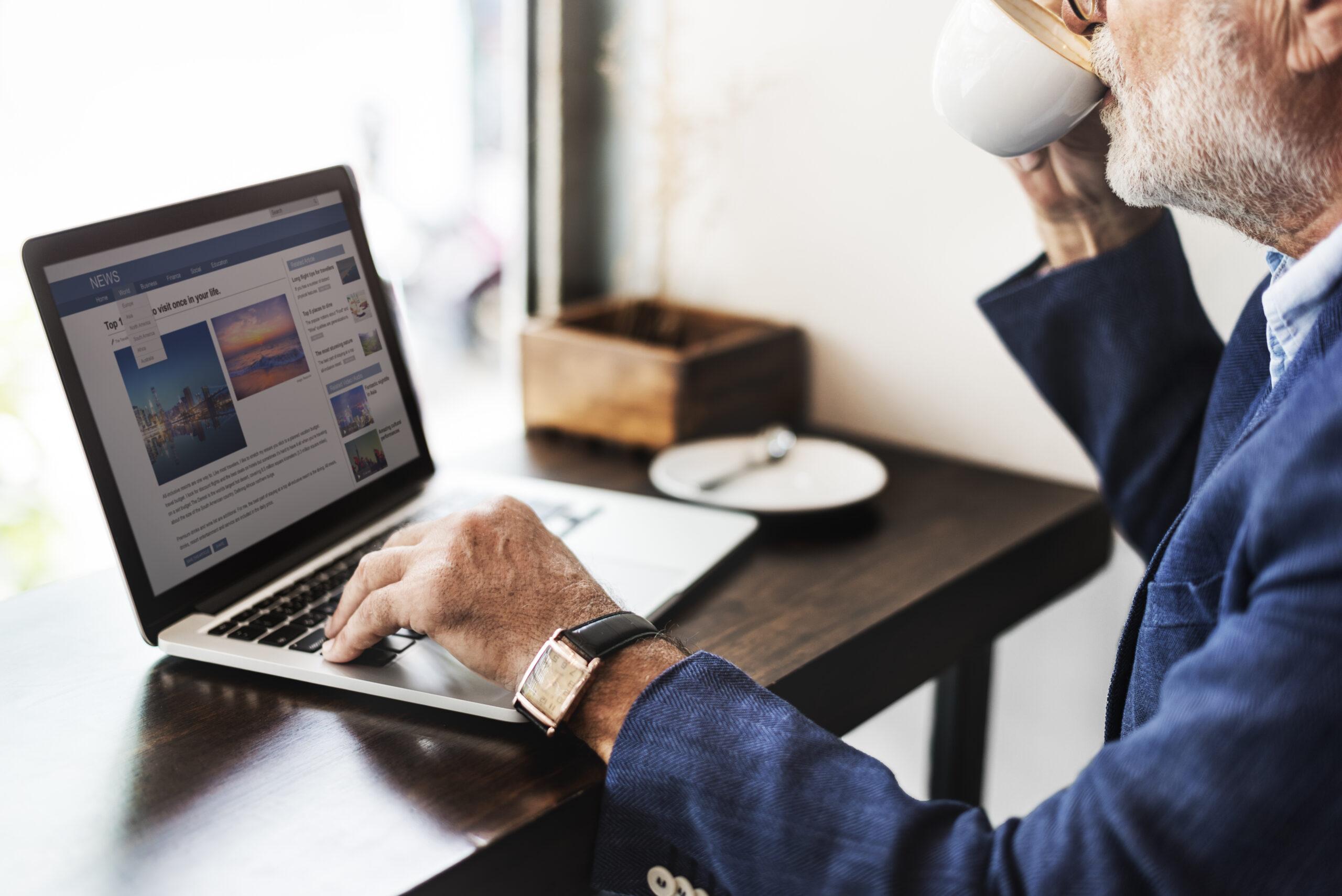 Mężczyzna w garniturze przegląda przy kawie artykuły na laptopie