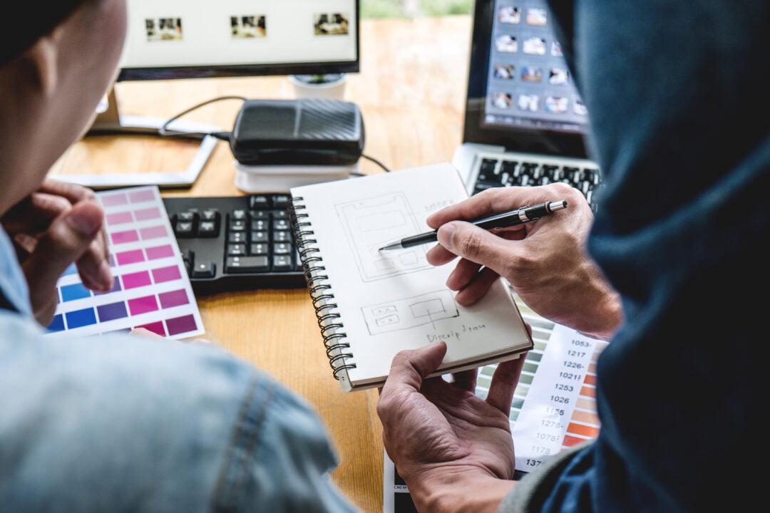 Przełożony tłumaczy pracownikowi plan działania rozrysowany na kartce