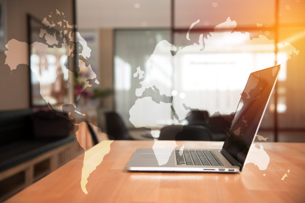 Mapa świata na tle laptopa obrazująca zalety pracy zdalnej